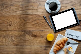 Breakfast with digital tablet on a wooden background with space